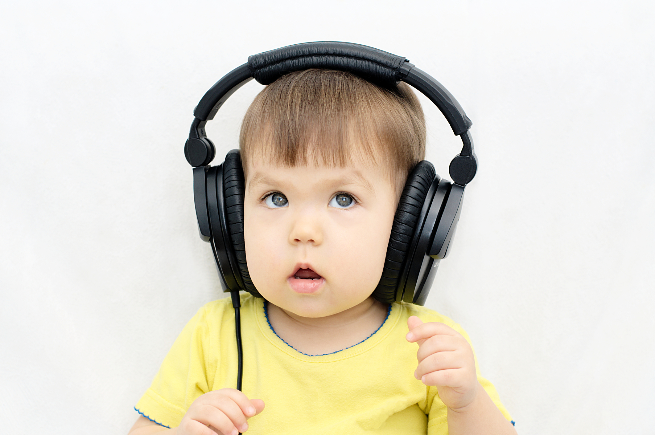 Image of a baby listening to earphones.