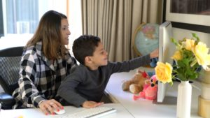 Preschool boy and mother interact with tutor during online language lesson.