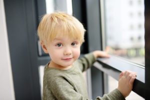 Blonde toddler boy touching window sill.
