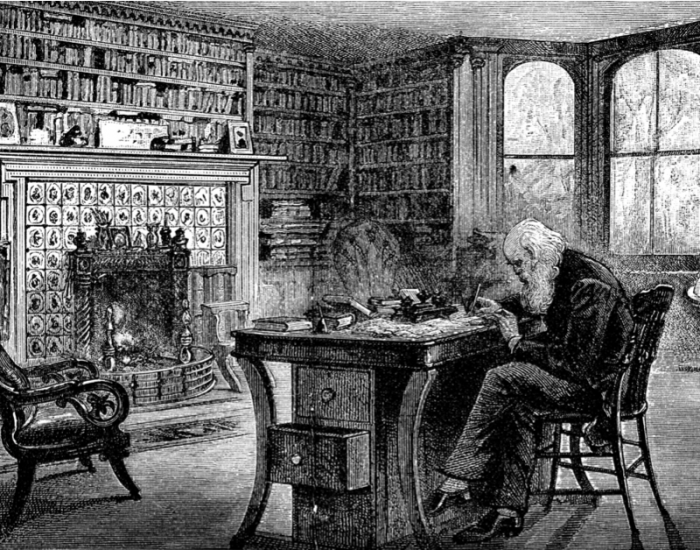 Image of Santa Claus working at a desk in his library.